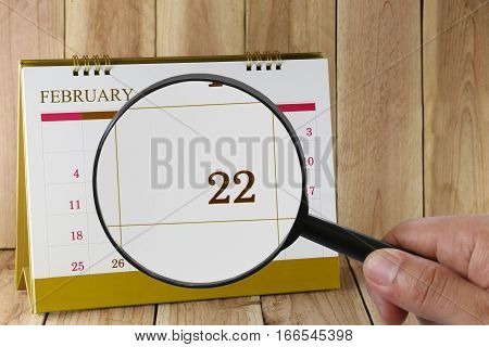 Magnifying glass in hand on calendar you can look Twenty-two day of monthFocus number Twenty-two in FebruaryConcept in business and meetings.