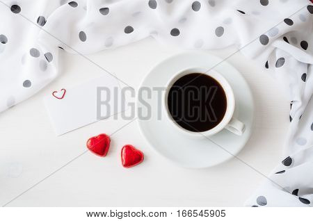 St Valentines day background - cup of coffee blank love card and two heart shaped candies, flat lay of St Valentines day still life. St Valentines background with concept of celebration of St Valentines day