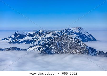 Summits of the Swiss Alps rising from sea of fog, wintertime view from Fronalpstock mountain in the Swiss Canton of Schwyz.