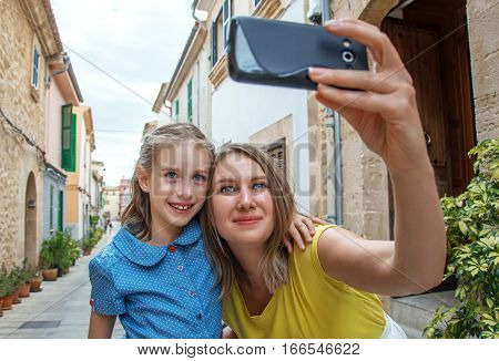 Mother And Daughter Taking Selfie In Old Town.