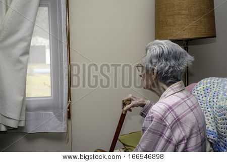 elderly woman looking out window hoping some one will come and visit