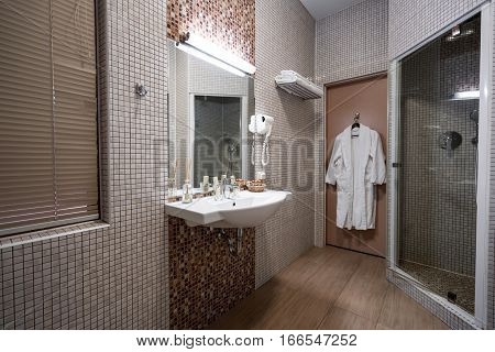 Fine hotel bathroom interior in beige color with bathrobe hanging on the door