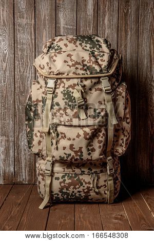 travel backpack khaki color on a wooden background.