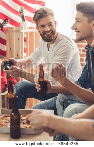 Attractive guys are playing video games drinking beer talking and smiling while sitting on couch at home