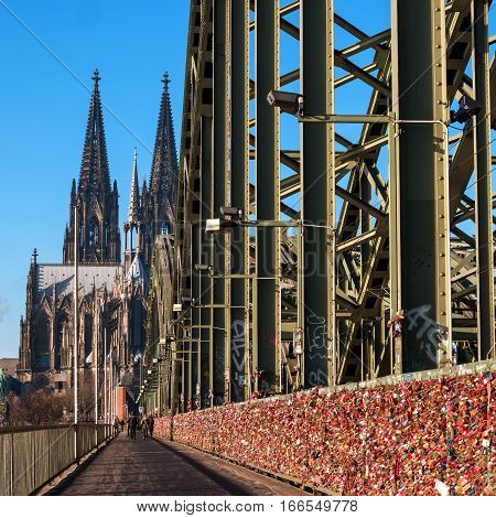 Cologne, Germany - January 19, 2017: Locks of love on the fence of the Hohenzollern Bridge. Hohenzollern Bridge in Cologne becomes a place of pilgrimage for young couples. In the background is the Cathedral of Cologne.