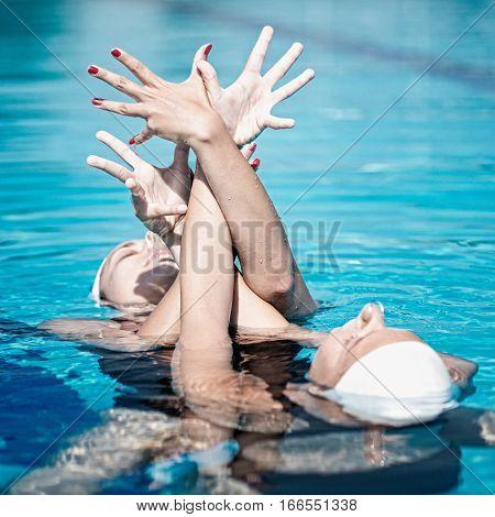 Synchronized swimming performance, toned image, blue image