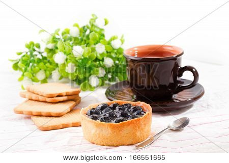 Breakfast with bilberry cake. Bilberry cake cookies and a cup with tea on a light table. Flowers on a background