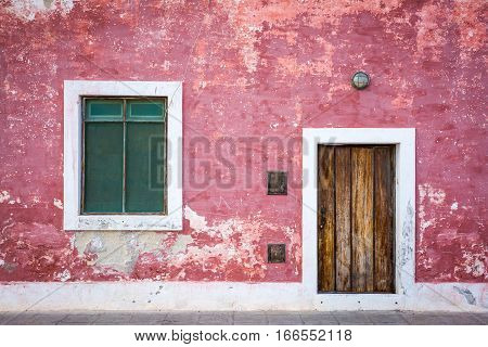Beautiful red and pink old colonial facade of building made by Portuguese people on Island of Mozambique in the north of Mozambique. Neglected and scruffy building has its charm and composition of window and doors is just perfect