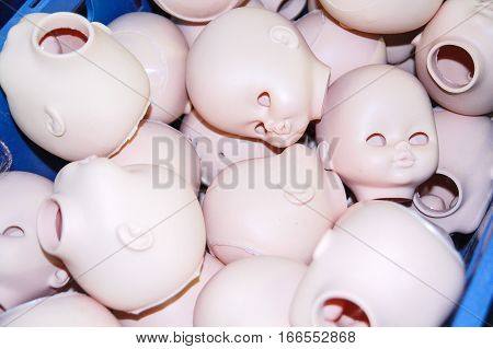 few heads of dolls without eyes are in the box