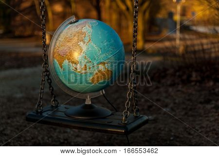 Globe put on a playground swing, representing a fine balance