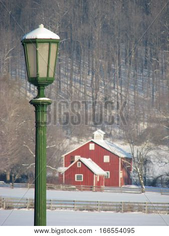 Green lamp post and red barn covered in snow on a sunny winter day