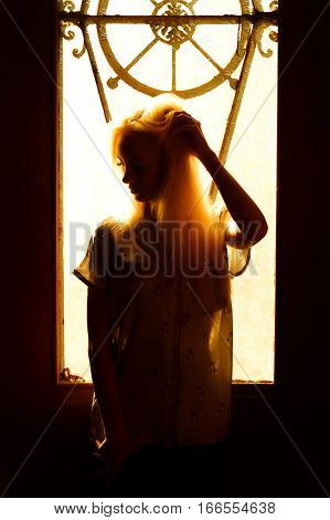 Beautiful young blonde girl with a pretty face and beautiful eyes. Dramatic portrait of a woman in the dark. Dreamy female look in twilight. Female silhouette in the shadows.
