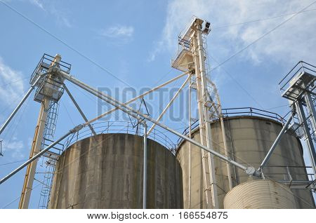 Industrial grain silos against clouds and blue sky