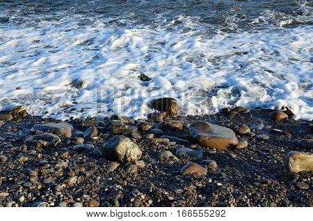 Seawater foam on a raised rocky shore.