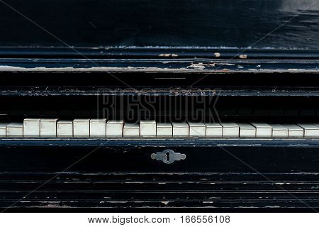 Vintage old piano. Worn piano keys. Black piano close up.