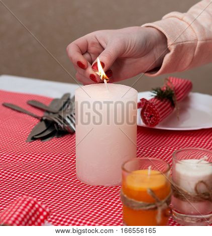 The white candle stands on the table. Festive composition with Lighted candles. Christmas table decoration. A beautiful table setting, red table cloth, tablecloth in the box. Christmas dinner.
