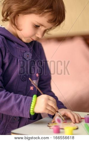 Little girl painting wooden toy at home