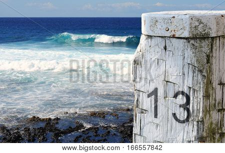 Mooring post or bollard 13 in front of deep blue ocean and waves