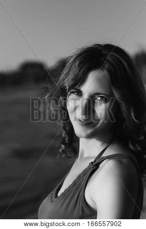 Black and white photo at sunset of a beautiful girl with curly hair and a beautiful smile.