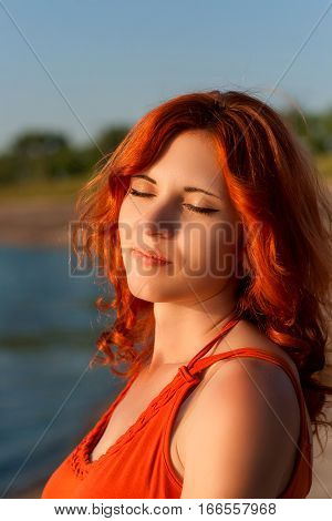 Cute girl with curly hair and a beautiful smile at sunset