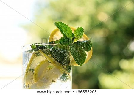 Mojito cocktail with mint and lemon in a highball glass on natural background