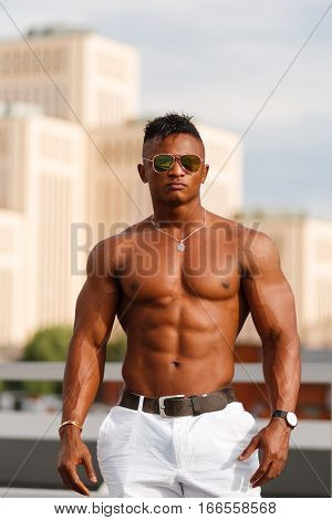 Hot Beautiful black guy with bulging muscles posing against the backdrop of the urban landscape Man fitness model with a beautiful body on the background of the city Shirtless Hunk man without a shirt