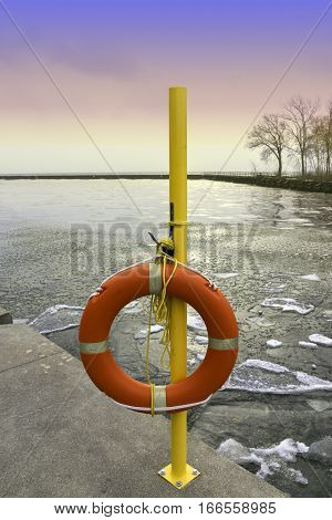 Emergency life preserver hanging on a yellow pole by an icy winter lake at sunset