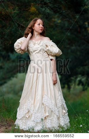 Beautiful woman in vintage dress beige. Cute girl in long dress walking in a pine forest. The style of the Queen Princess.