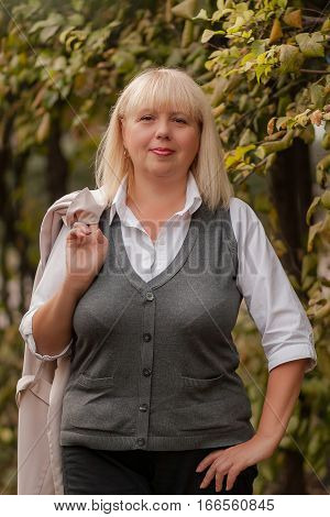 Senior business woman walking in the autumn Park. A woman in a classic clothing style. Elegant woman in a costume. Business lady.