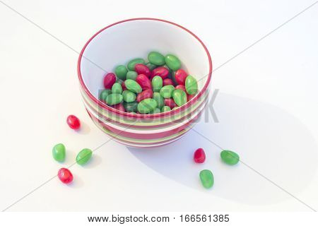 Red and green jelly beans in a Christmas colored striped bowl