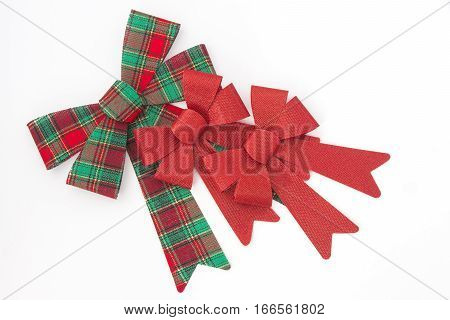 Red and green plaid bow with two red holiday bows arranged on a white background