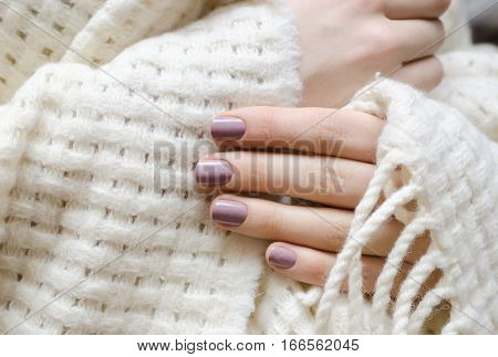 Female hand with natural pink nail design holding light plaid.