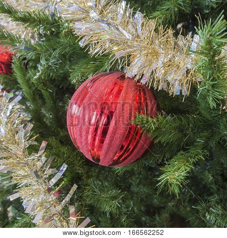 Party tinsel and red glittery ornament on festive holiday Christmas tree closeup