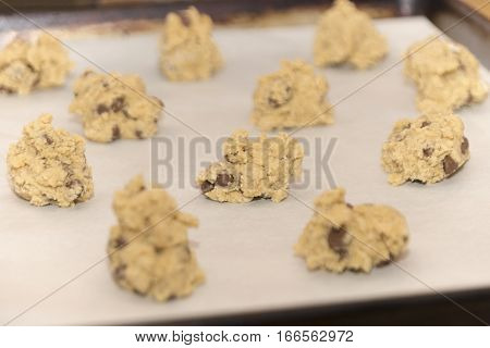 Raw chocolate chip cookie dough balls ready to be baked in the oven on baking sheet