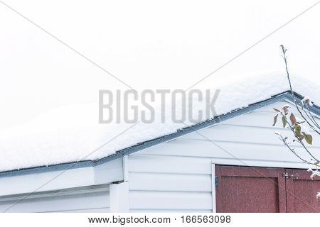Snow covered rooftop of rustic country shed background space for text