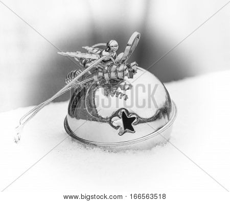 Silver ornamental sleigh bell sitting in the winter snow white vignette