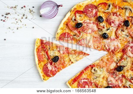 Hot true pepperoni italian pizza on the white table with spices. Delicious fresh homemade pizza with salami cheese mushrooms tomatoes pepper. Italian food concept. Top view. Copy space.