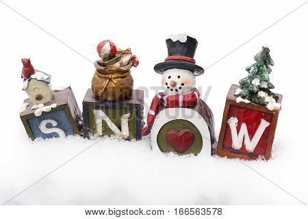 Four vintage painted decorative blocks with snowman that spell the word snow arranged on snow