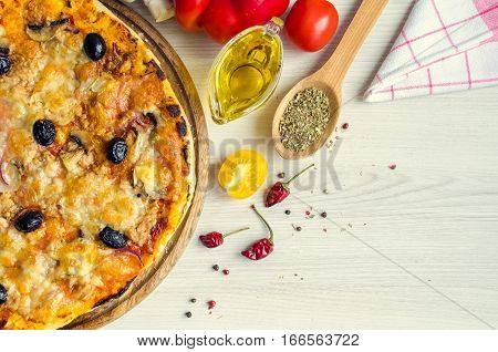 Vegetarian Italian pizza with tuna on white table with spices and olive oil. Delicious pizza with tuna cheese Mozzarella mushrooms onion and olives. Italian food concept. Top view. Copy space.