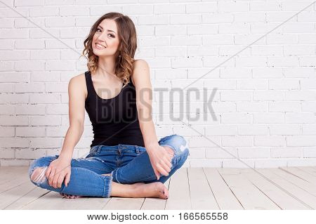 Pretty sexy woman model with amazing body beautiful long legs seating on the floor wearing denim jeans black lingerie top, posing looking aside