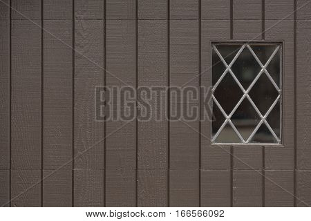 Brown Garage Door with Strong Vertical Lines and Diamond Paned window