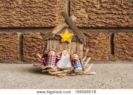 Handmade Manger craft with Jesus, Joseph and Mary, on brick background