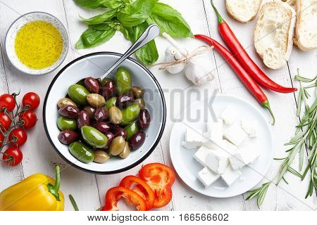 Mediterranean cuisine ingredients: fresh olives mix, rosemary twigs, green basil leaves, cherry tomatoes, pepper, feta cheese, ciabatta bread and olive oil on white wooden background