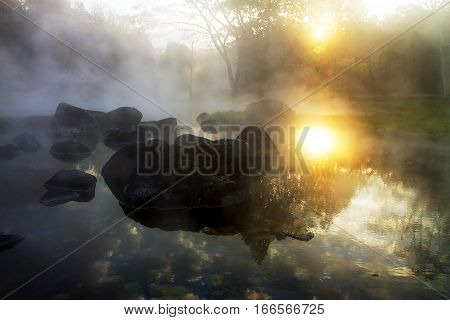 Sunrise whit steam and pond in the Park Nation country of Thailand.