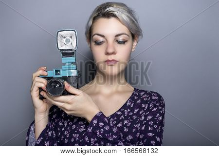 Female hipster as an art student or photographer with a vintage retro plastic film camera. The antique is used to learn the basic fundamentals of photography or for nostalgia.