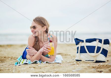 Woman Relaxing And Sunbathing On Beach