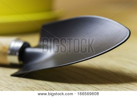 Closeup of gardening trowel with yellow planter simple spring background