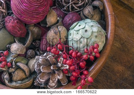 Closeup of wooden bowl with large potpourri berries twigs berries and twine natural pieces