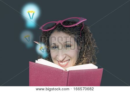 Ideas and education concept young woman with quirky glasses a book and a pencil behind ear lightbulbs rising