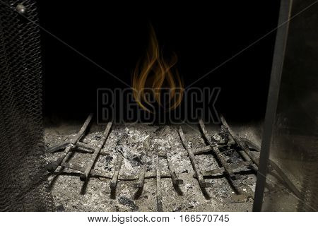 Empty fireplace full of ashes glowing ghost of past fire above dark background